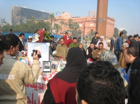 February 2011 Tahrir Square commemoration of martyrs. Burned building in background is headquarters of Mubarak's now-outlawed political party.