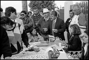 TIJUANA BAJA CALIFORNIA NORTE, MEXICO - 1993 - Workers vote in a union election outside the Tijuana maquiladora of Plasticos Bajacal.  Voting is public, and workers have to declare aloud whether they're voting for the company union or their own independent union.  Sr. Mandujano, head of the labor board in Tijuana and an ally of the companies and the company unions, points to a worker and demands that he say which union he's voting for.  Company  and company union officials look on, along with Carmen Valadez, representative of the independent union.  The election was called off halfway through.